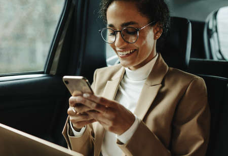 Smiling woman traveling by a car. Businesswoman sitting on backseat of a car and reading text message.