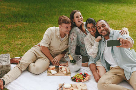 Group of happy friends having fun together and taking selfie using mobile phone. Young people on picnic taking self portrait of with smart phone.