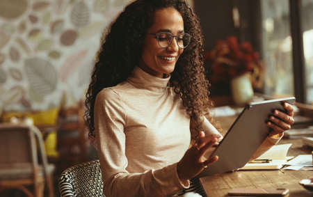 Woman sitting at cafe using her digital tablet. Smiling female in casuals working on her tablet pc from a coffee shop.