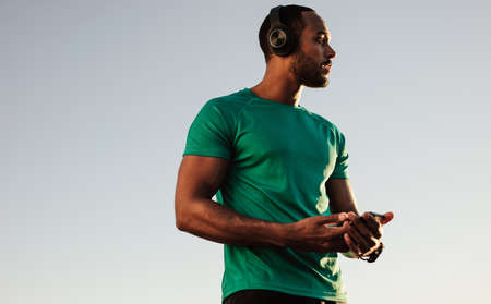 Close up of an afro american man in tshirt standing outdoors. Male athlete listening to music during workout.