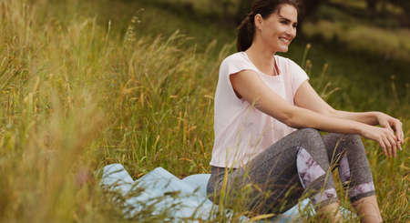 Portrait of a smiling woman sitting in park. Cheerful female sitting in the meadows enjoying nature.