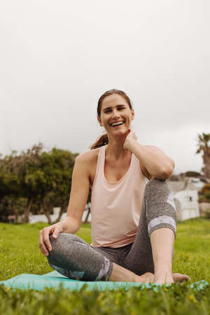 Close up of a smiling woman sitting on yoga mat in a park. Fitness woman relaxing after workout outdoors on a cloudy day.