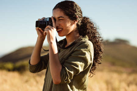 Close up of a woman taking photo using a digital camera. Tourist woman doing nature photography on a sunny day.