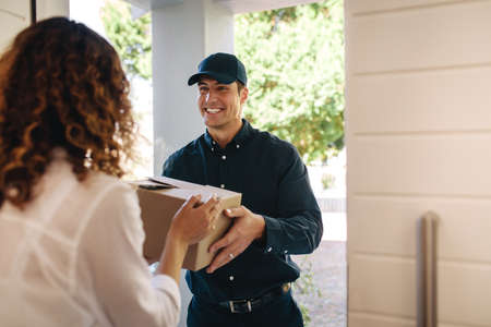 Smiling delivery man handing over a box to female at home. Courier worker delivering a parcel to woman. Banque d'images