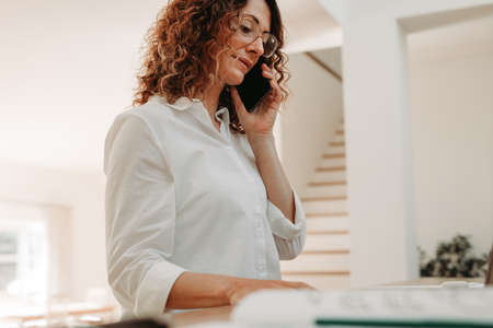 Female sitting at home making a phone call while working on a laptop. Businesswoman with curly hair wearing eyeglasses working from home. Banque d'images