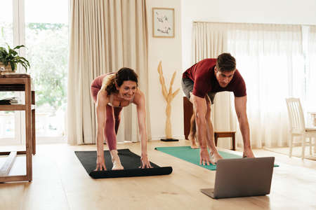 Couple exercising at home following instructions on laptop. Man and woman in sportswear working out watching fitness video tutorial online. Banque d'images