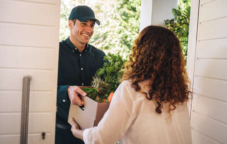 Delivery man hands over box of groceries at the house door. Delivery employee delivering a box of fruits and vegetables to a woman.