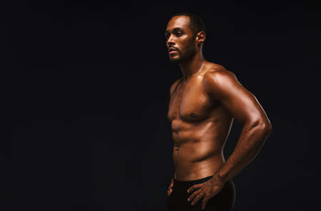 Portrait of african american man standing on black background. Bare chested muscular athlete standing with hands on waist.