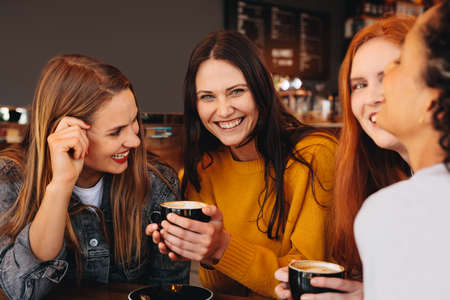 Woman holding a cup of coffee sitting with friends at a coffee shop. Young women sitting at a restaurant having coffee.