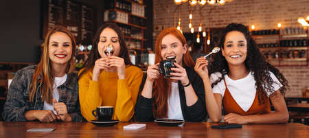 Friends making funny faces in a cafe. Crazy young women sitting together in a coffee shop. Banque d'images