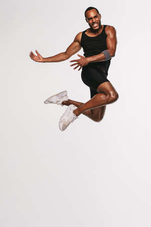 African american athlete doing fitness exercise. Fit man jumping high in air during workout. Banque d'images