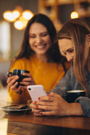 Two young women using a smart phone at coffee shop. Two smiling female friends using a mobile phone at a cafe