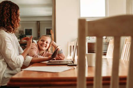 Girl sitting with her mother at home. Mother holding a digital tablet talking with her daughter while working from home.