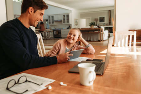 Happy young man sitting with her daughter at table using a digital tablet together at home.