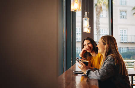 Two female friends talking at a coffee shop. Young women sitting at a cafe and smiling.