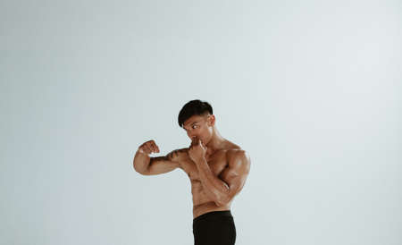 Fit male practising shadowboxing. Masculine young male athlete working out on white background.