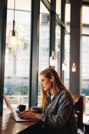 Woman looking busy working on laptop at a cafe. Female wearing earphones sitting in coffee shop using laptop.