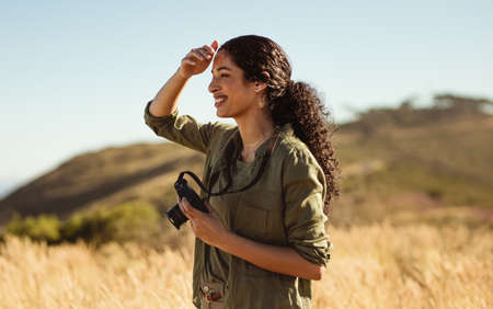 Woman standing outdoors holding a camera. Female photographer out to shoot nature on a sunny day.