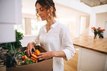 Woman in her kitchen with a box full of organic vegetable. Female checking the fresh vegetables and fruits in a delivery box.