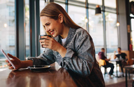 Beautiful woman looking at her phone and drinking coffee at cafe.  Female in casuals sitting in a cafe looking at her smartphone and smiling.