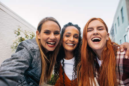 Three young women having fun on city street and taking selfie. Multiracial female friends enjoying a day around the city.