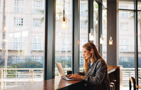 Woman sitting at a cafe table working on laptop. Woman doing her work sitting at a coffee shop. Banque d'images
