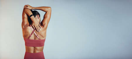 Rear view of fitness woman doing arm stretching exercises. Female athlete doing warm up before workout.