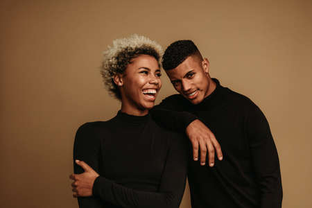 Happy couple standing together and laughing. African american man and woman having fun standing against brown background.