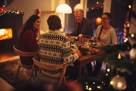 European family enjoying dinner on Christmas eve. Family having a Christmas eve dinner together in warm and cosy home.