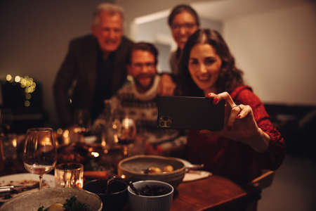 Woman taking selfie with family on christmas eve. Female making memories during Christmas dinner. Stock fotó