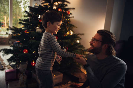 Father and son by a Christmas tree indoors. Family at home celebrating Christmas.