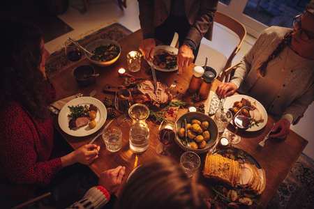 Top view of dining table during Christmas dinner at scandinavian home. Senior man serving roasted turkey to family. Stock fotó