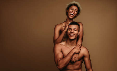 African american couple together on brown background. Cheerful woman standing behind shirtless muscular man.