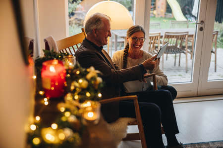 Senior couple using tablet computer for video call their family on a Christmas eve. Senior man and woman looking at digital tablet and smiling during a video call. Stock fotó