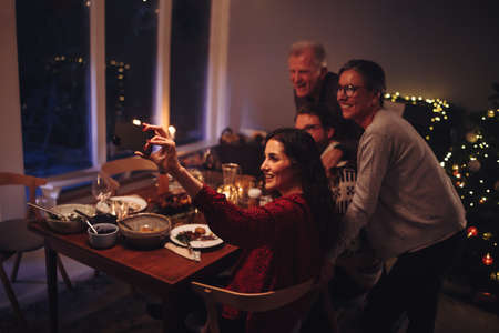Family taking selfies at Christmas dinner table. Woman clicking selfie portrait with family on Christmas eve at home.