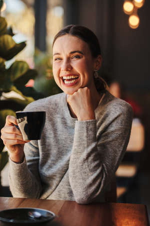 Attractive woman drinking coffee at cafe. Female having a cup of coffee and laughing at coffee shop. Banque d'images