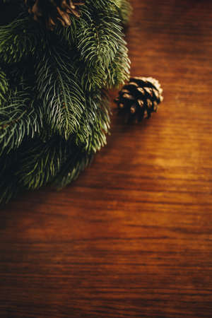 Advent wreath and pine cone on wooden background. Christmas decoration on a table top.