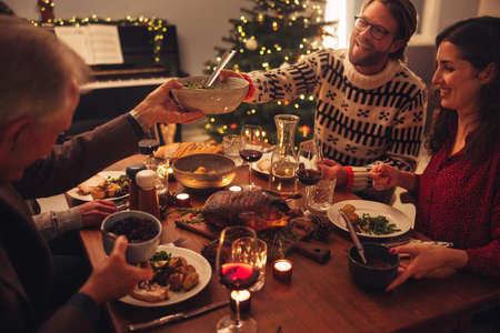 Family having a Christmas eve dinner together inside their home. European family enjoying dinner at Christmas eve.