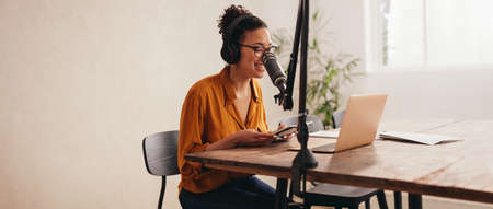 Woman podcaster making a podcast from home studio. Female working from home recording a podcast on a laptop. 免版税图像