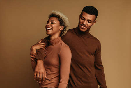 Fashionable african american couple standing together. Smiling couple in love together on brown background.