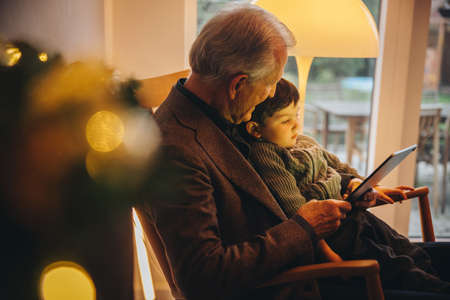 Senior man with her grandson having a video call on digital tablet. Grandfather and grandson sitting on chair using a digital tablet during christmas.