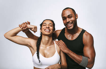 Smiling couple having fun at the gym after workout. Happy woman in fitness wear showing her biceps with her male friend by her side.