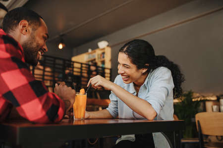 Woman sitting at cafe with her boyfriend and smiling. Couple on date at coffee shop. Stock fotó