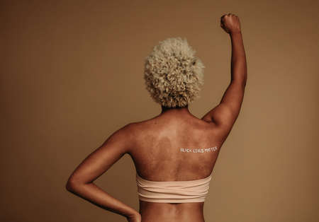 Rear view portrait of african american woman standing with arm raised on protest. Woman expressing her views with words black lives matter written on her back.