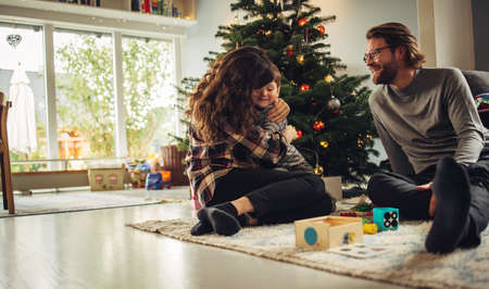 Small family having happy time together on Christmas. Loving scandinavian family sitting by Christmas tree at home. Stock fotó