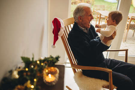 Senior man having fun with small boy at home during christmas. Grandfather sitting on chair playing with his grandson. Stock fotó