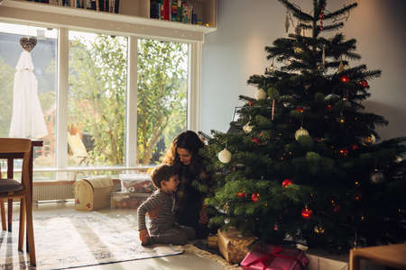 Mother and son sitting by Christmas tree at home. Mother with her child celebrating Christmas.