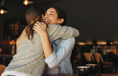 Cheerful female friends embracing each other and greeting at a cafe. Two women meeting at a coffee shop hugging each other.