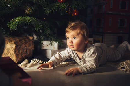 Cute baby boy lying by christmas tree at home. Boy looking at christmas gifts under the christmas tree. Stock fotó