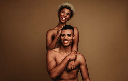 Portrait of smiling african american couple together. Smiling shirtless man with woman on brown background. Stock fotó